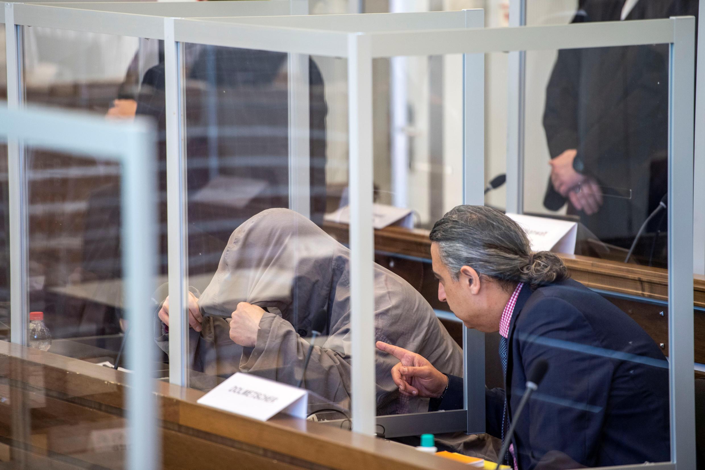 أحد المتهمين إياد أ. وهو يخفي وجهه قبل المحاكمة الأولى لبعض المشتبه بهم الذين عملوا سابقا  في الأجهزة الأمنية التابعة للرئيس السوري بشار الأسد، يتم محاكمتهم في ألمانيا بتهمة ارتكاب جرائم ضد الإنسانية، في كوبلنز، ألمانيا ، 23 أبريل / نيسان 2020.