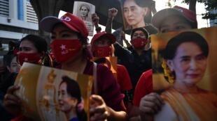 متظاهرون يرفعون صورة للزعيمة البورمية أونع سان سو تشي خلال تظاهرة أمام السفارة البورمية في بانكوك في 1 شباط/فبراير 2021.