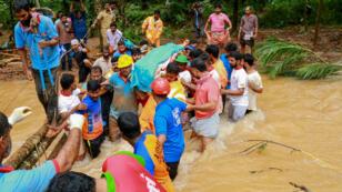 Des secouristes transportant un corps après un glissement de terrain à Kavalappara, dans le district de Malappuram de l'État du Kerala, au sud de l'Inde, le 11août2019.