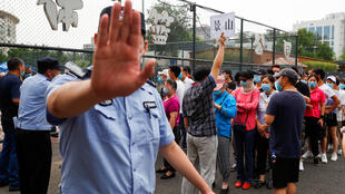 A police officer gestures at a photographer as people line up to get a nucleic acid test at a sport center after a spike of cases of the coronavirus disease (COVID-19), in Beijing, China June 17, 2020.
