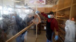 عامل فلسطيني في مخبز بقطاع غزة يرتدي كمامة ويقف خلف حاجز بلاستيكي يفصله عن زبائنه للوقاية من فيروس كورونا، 22 مارس/آذار 2020.