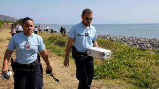 Des gendarmes rapportant des débris de la plage où a été trouvé un fragment d'aile.