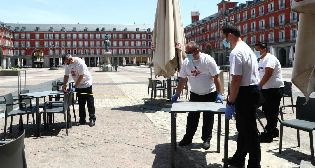 Dos trabajadores utilizan cinta métrica para medir la distancia de seguridad en las mesas de una terraza en la plaza Mayor de Madrid durante el primer día de desconfinamiento. Madrid, España, el 25 de mayo de 2020.