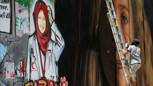 Un artista extranjero pinta un mural que representa a la adolescente palestina Ahed Tamimi detenida por las autoridades de Israel, junto a un mural de la enfermera palestina fallecida Razan Al-Najar, en Belén, en la ocupada Cisjordania, el 25 de julio de 2018