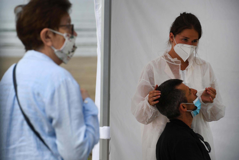 Personal médico recolecta una muestra de un hombre en un centro de pruebas móvil para el nuevo coronavirus en la playa de Pentrez en Saint-Nic, en el oeste de Francia, el 12 de agosto de 2020.