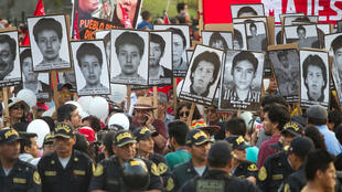 Manifestantes muestran carteles con los rostros de las víctimas de las matanzas por las que fue condenado Fujimori durante una multitudinaria marcha contra su indulto en Lima (Perú). 30/01/2018.
