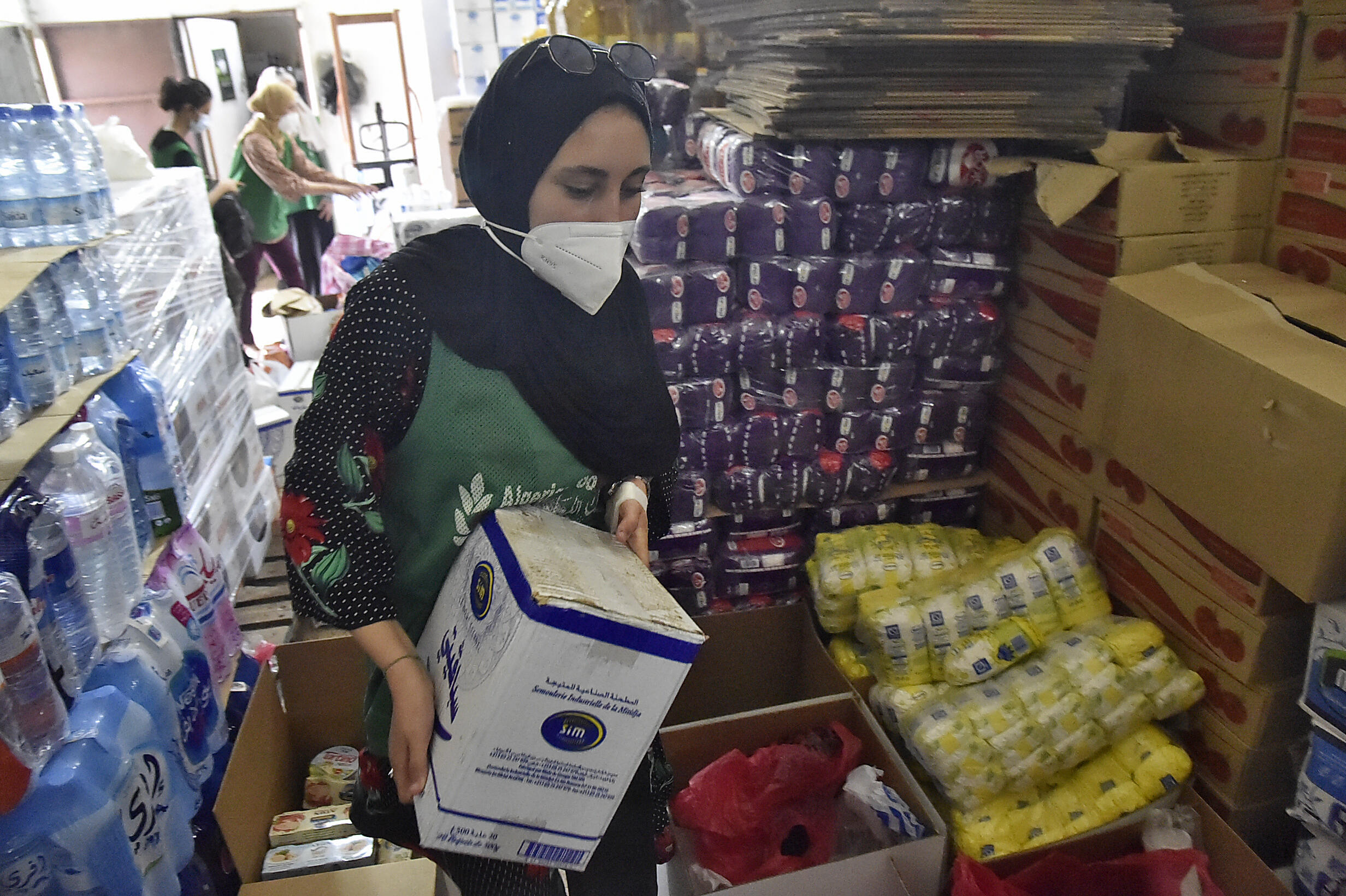 Des volontaires de l'ONG Association Citra participent à un effort avec la Banque alimentaire algérienne pour envoyer des colis d'aide aux victimes de l'incendie régional de Kabili le 12 août 2021 dans la capitale algérienne, Alger.