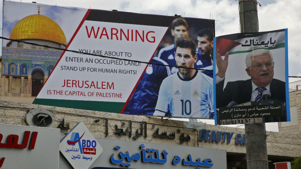 Una foto tomada el 5 de junio de 2018 muestra un cartel erigido en una calle principal de la ciudad cisjordana de Hebrón junto a un retrato del presidente palestino Mahmud Abbas, en el que denunciaban el partido amistoso de fútbol entre Argentina e Israel y llamando a la estrella de Argentina, Lionel Messi, a boicotear el partido.