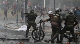 La policía antidisturbios choca se enfrenta a los manifestantes durante una protesta contra el Gobierno en Santiago de Chile, Chile, el 23 de octubre de 2019.