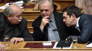 Discussion entre le Premier ministre grec Alexis Tsipras (droite), Yannis Dragasakis (milieu) et le ministre de l'Intérieur Nikos Voutsis (gauche), le 30 mars 2015 à Athènes.