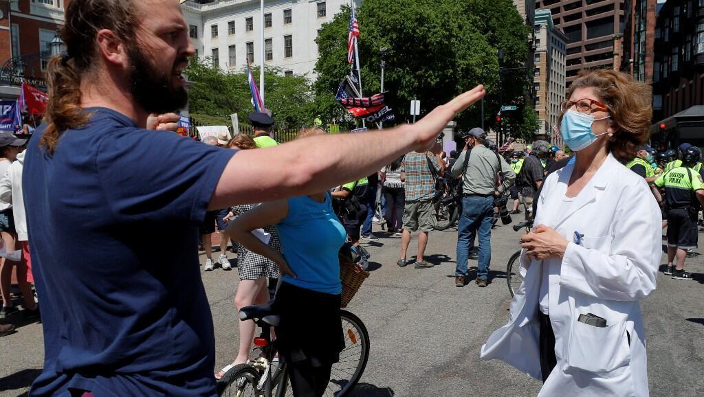 Un hombre que protesta contra las medidas de aislamiento discute con una doctora sobre el uso de mascarilla para evitar el contagio de Covid-19. En Boston, Massachusetts, Estados Unidos, el 30 de mayo de 2020.