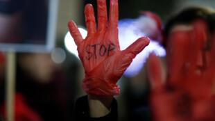 """امرأة تحمل شعار """"قف"""" على قفاز أثناء مظاهرة للاحتجاج على قتل النساء والعنف ضد النساء في نانت، فرنسا، 25 نوفمبر/ تشرين الثاني 2019."""
