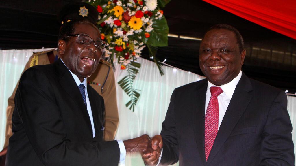 El presidente de Zimbabwe, Robert Mugabe, bromea con el primer ministro Morgan Tsvangirai después de firmar la nueva constitución de Zimbabwe en la capital, Harare, el 22 de mayo de 2013.