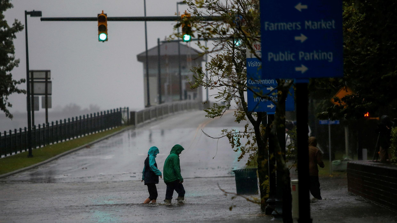La gente camina en una calle local cuando el agua del río Neuse comienza a inundar casas debido a la llegada del huracán Florence a la costa en New Bern, Carolina del Norte, EE. UU., el 13 de septiembre de 2018.