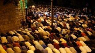 فلسطينيون يؤدون الصلاة أمام باب الأسباط المؤدي للحرم القدسي في القدس الشرقية المحتلة مساء 26 تموز/يوليو 2017