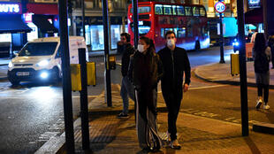 A couple wearing face masks walk down Clapham High Street, as the number of coronavirus cases grow around the world, in London, Britain March 16, 2020.