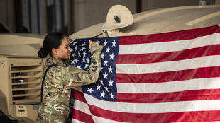 جنجية أميركية ترفع العلم الأميركي في قاعدة عسكرية في ريملان في شمال شرق سوريا بتاريخ 28 تموز/يوليو 2020