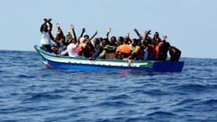 Migrantes en un bote de madera esperan ser rescatados por la organización SOS Meditérranée y Médicos Sin Fronteras durante una operación de búsqueda y rescate con el buque de rescate Aquarius en el Mar Mediterráneo, el 10 de agosto de 2018.