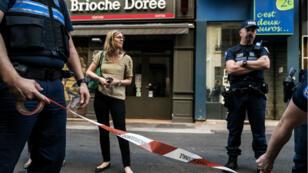 """Des policiers établissent un cordon de sécurité devant la """"Brioche dorée"""" du centre de Lyon, au lendemain de l'explosion."""