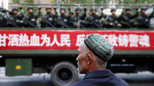 A Uighur man looks on as a truck carrying paramilitary policemen travels along a street during an anti-terrorism oath-taking rally in Urumqi, in China's Xinjiang province, on May 23, 2014.