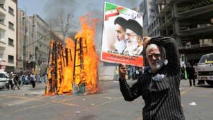 Un manifestant brandit une pancarte représentant le guide suprême iranien Ali Khamenei (à droite) et le grand ayatollah Ali al-Sistani, le 10 juillet 2015 à Téhéran.