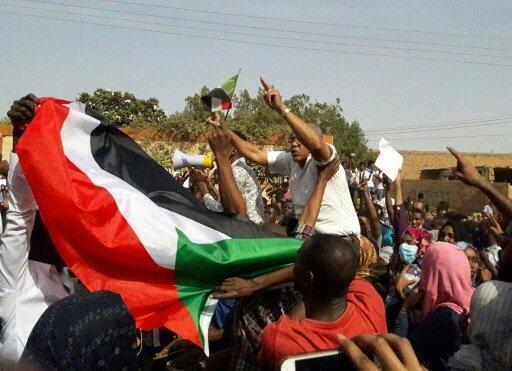 متظاهرون يلوحون بالعلم السوداني خلال تجمع ضد الرئيس عمر البشير في أم درمان في 31 يناير/كانون الثاني 2019