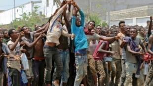 مهاجرون محتجزون في ملعب كرة القدم أثناء تلقيهم الغذاء والمياه في 23 نيسان/أبريل