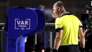 El árbitro argentino Néstor Pitana revisa una jugada en los monitores del VAR durante el partido Brasil-Bolivia en el estadio Morumbí de Sao Paulo, el 14 de junio de 2019.