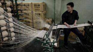 Un empleado del fabricante de uniformes para artes marciales KuSakura revisa una máquina de coser antigua el 25 de febrero de 2020 en la fábrica en Kashiwara, Japón, el 25 de febrero de 2020