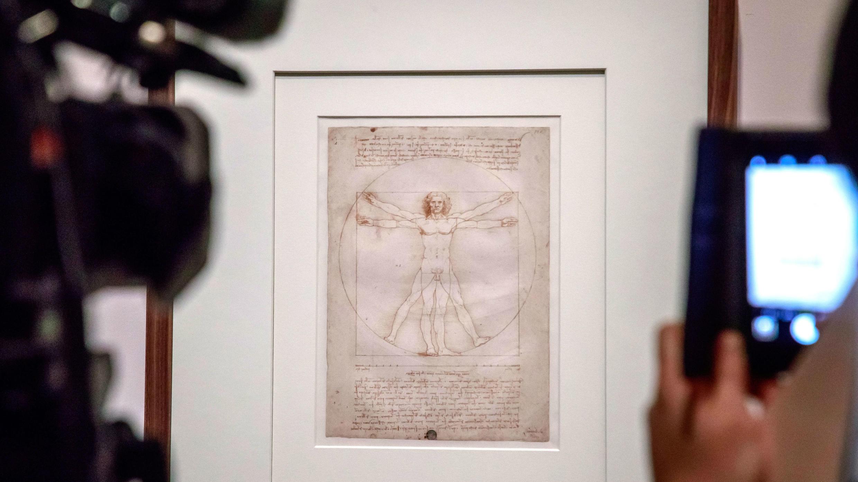 La gente toma fotografías del dibujo titulado 'El Hombre de Vitruvio', del artista renacentista italiano Leonardo Da Vinci, exhibido durante una exposición en el Museo del Louvre en París, Francia, el 22 de octubre de 2019.