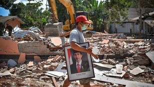 Un hombre lleva una foto enmarcada del presidente indonesio Joko Widodo de una escuela dañada por un terremoto en Gunungsari, Lombok , Indonesia el 12 de agosto de 2018.