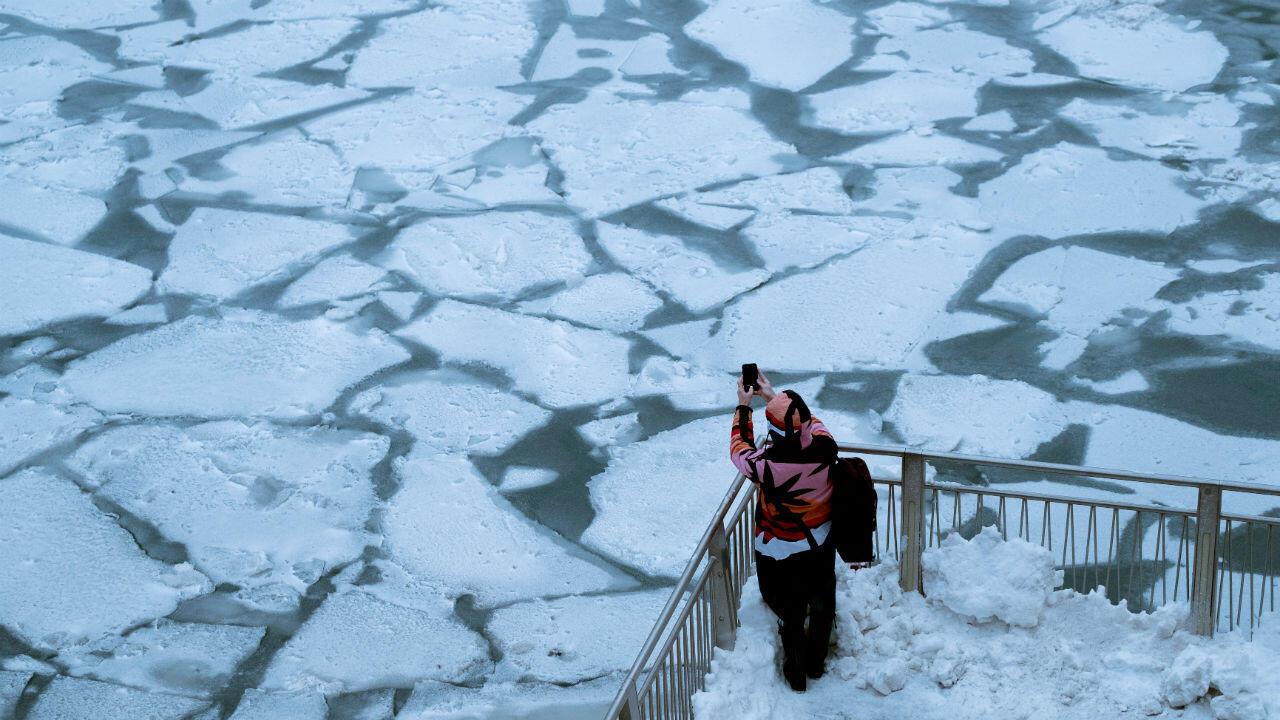 Un turista se detiene para tomar una foto junto al río Chicago, congelado por las bajas temperaturas. 29 de enero de 2019.