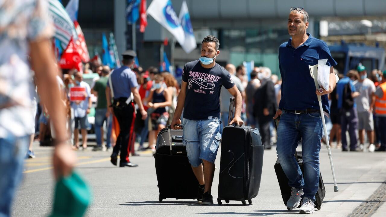Archivo: Un par de viajeros camina a las afueras del Aeropuerto de Roma-Fiumicino, al tiempo que decenas de personas protestan por mejores condiciones laborales, tras la crisis del Covid-19 en este país. En Roma, Italia, el 8 de julio de 2020.