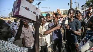 Young Sudanese protesters mimic journalists -- complete with a cardboard mocked up camera and a plastic bottle to represent a microphone -- to poke fun at state TV for failing to cover demonstrations