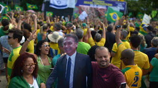 Un hombre se toma una selfie junto a un muñeco de cartón de Jair Bolsonaro durante una protesta a su favor cerca a las playas de Copacabana en Río de Janeiro, Brasil, el 26 de mayo de 2019.