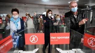 أشخاص يرتدون أقنعة واقية في محطة مترو في موسكو في 12 أيار/مايو 2020