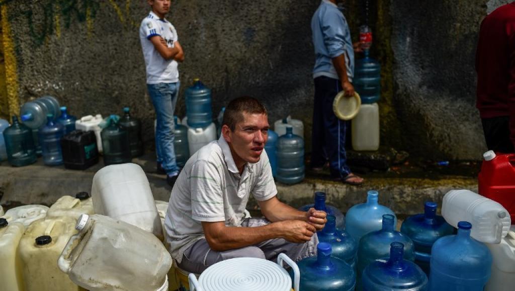 Venezolanos esperan con bidones para poder cargar agua en el cerro El Ávila, en Caracas.