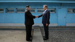 Kim Jong-un (à g.) et Moon Jae-in se serrent la main au-dessus de la frontière entre les deux Corées, le 27 avril 2018.