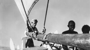 """Photo non datée de l'écrivain et aventurier Henry de Monfreid (à gauche) sur son voilier l'""""Obock""""."""