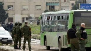 حافلة تنقل مسلحين وعائلاتهم خلال عملية إجلاء من حي الوعر في حمص في 18 آذار/مارس 2017