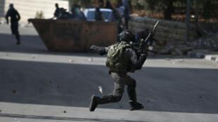 Un soldat israélien face à des lanceurs de pierres palestiniens à Beit El, près de Ramallah en Cisjordanie, le 8 octobre 2015.