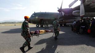 Soldados evacuan a una mujer en camilla a un avión militar en el aeropuerto Mutiara Sis Al-Jufri en la ciudad de Palu, azotada por el terremoto y el tsunami de Indonesia, 4 de octubre 2018.
