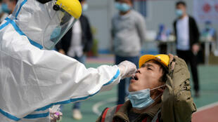 A worker in a protective suit collects a swab on April 7, 2020, from a construction worker for nucleic acid test in Wuhan, Hubei province, the epicentre of the novel coronavirus disease (Covid-19) outbreak in China,.