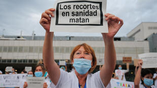 """""""Los recortes en sanidad matan"""", se lee en un cartel mostrado por una trabajadora sanitaria delante del Hospital Vall d'Hebrón, en Barcelona, el 12 de mayo de 2020, Día Mundial de la Enfermería"""
