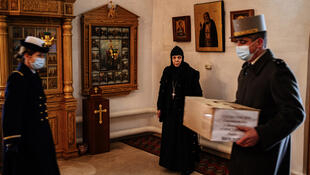 Military attache of the French embassy in Moscow Brigadier General Ivan Martin (R) carries a box containing remains of Russian and French soldiers who died during Napoleon's 1812 retreat, in a small church in the monastery of John the Precursor in the town of Viazma, on February 8, 2021.