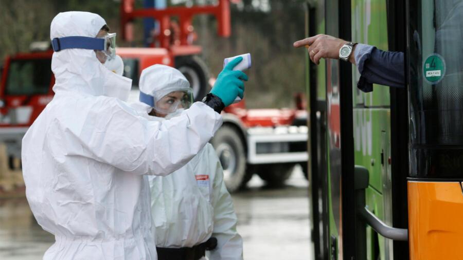 Des policiers en tenue de protection vérifient la température d'un passager d'un bus à la frontière tchéco-allemande au passage de Rozvadov, en République tchèque, le 9 mars 2020.