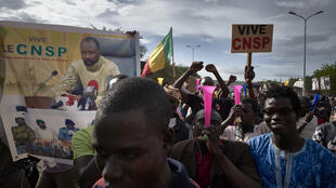 Supporters of the junta, which calls itself the CNSP (National Committee for the Salvation of the People), walk past a banner depicting its leader Assimi Goita in a rally in Bamako on Wednesday