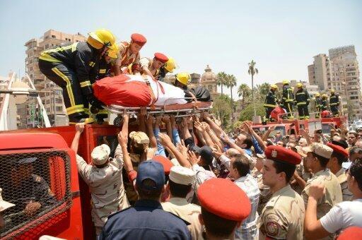 """رجال شرطة وإطفاء ينزلون جثمان جندي قتل في شمال سيناء في اعتداء نفذه تنظيم """"الدولة الإسلامية"""" خلال تشييعه في المنصورة في 8 تموز/يوليو 2017"""