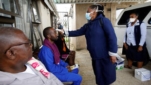 A health worker checks a man's temperature during a door-to-door testing in an attempt to contain the coronavirus outbreak in Umlazi township near Durban, South Africa on April 4, 2020.
