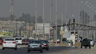 Des membres de l'organisation État islamique contrôlent un point de passage à Mossoul, le 17 juin 2014.